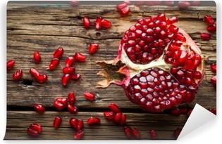 Fotomural Estándar Fruta de la granada jugosa sobre la mesa de madera