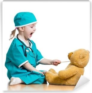 Vinyl-Fototapete Adorable Kind als Arzt spielt mit Spielzeug über Weiß gekleidet