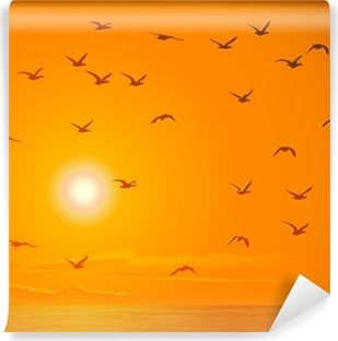 Vinyl-Fototapete Fliegende Vögel gegen orange Sonnenuntergang.