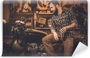 Vinyl-Fototapete Mann und Vintage-Stil Café-Rennläufer-Motorrad in der Garage