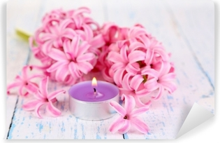 Vinyl-Fototapete Rosafarbene Hyazinthe mit Kerze auf Holzuntergrund