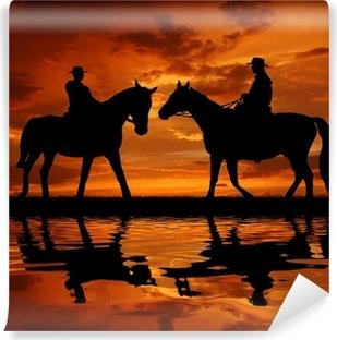 Vinyl-Fototapete Silhouette Cowboys mit Pferden in den Sonnenuntergang
