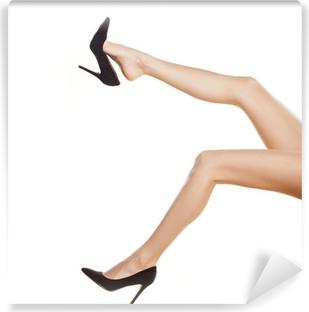 Vinyl-Fototapete Ziemlich weibliche Beine in schwarzen Schuhen mit hohen Absätzen auf weißem