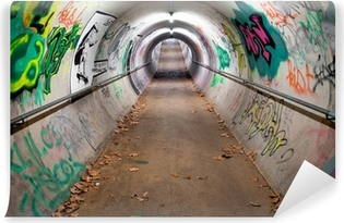 Fototapet av vinyl En lang gågatunnel dekket med graffiti og neonlys