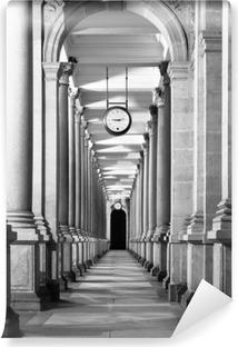 Lang colonnafe korridor med kolonner og ur hængende fra loftet. Klosterperspektiv. . Sort og hvidt billede. Vinyl Fototapet