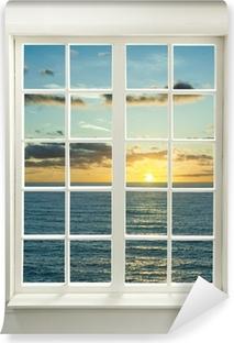 Moderne bolig vindue med solnedgang over havet og skyer Vinyl fototapet