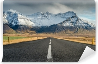 Fototapet av vinyl Perspektiv vei med snø fjellkjede bakgrunn i overskyet dag høst sesongen Island