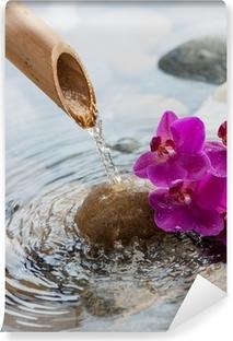 Fototapet av Vinyl Rinnande vatten på stenar bredvid blommor