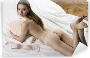 Sexet nøgen pige ligger på den hvide seng med pude i hendes arme Vinyl fototapet