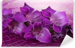 Fototapet av vinyl Vakker gladiolus blomst i vann på lilla bakgrunn