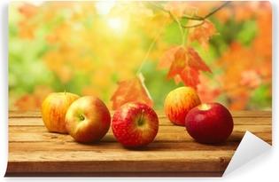 Fototapeta winylowa Jabłka na woodn tabeli nad jesiennym tle bokeh