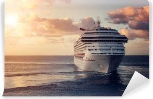 Fototapeta Winylowa Luksusowy statek wycieczkowy opuszcza port o zachodzie słońca