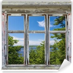Fototapeta winylowa Malowniczy widok widziany przez ramy okna starego