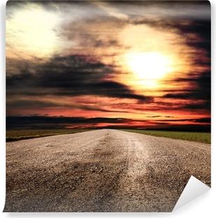 Fototapeta winylowa Polnej drodze w wiejskich na zachodzie słońca