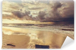 Fototapeta samoprzylepna Piękny zachód słońca z chmurami nad morzem i na plaży