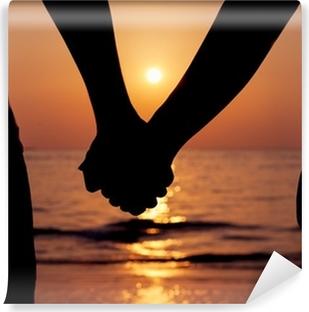 Vinylová Fototapeta Siluety páry drží za ruce na západ slunce.