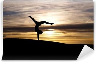 Fototapeta winylowa Sylwetka gimnastyczka o zachodzie słońca