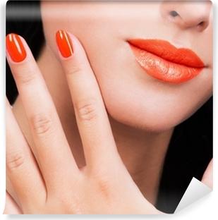Fototapeta winylowa Zbliżenie kobiet strony z pięknym pomarańczowe paznokcie na kobiecej twarzy