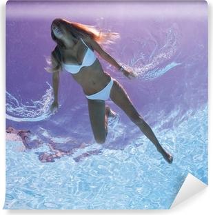 Vinylová Fototapeta Žena pod vodou v bazénu s podsvícením.