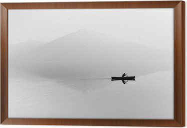 Fog over the lake. Silhouette of mountains in the background. The man floats in a boat with a paddle. Black and white Framed Canvas