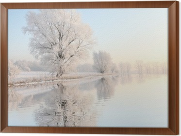 Frosty winter tree against a blue sky with reflection in water Framed Canvas
