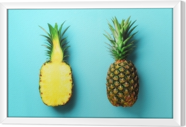 Whole pineapple and half sliced fruit on blue background. Top View. Copy Space. Bright pineapples pattern for minimal style. Pop art design, creative concept Framed Canvas