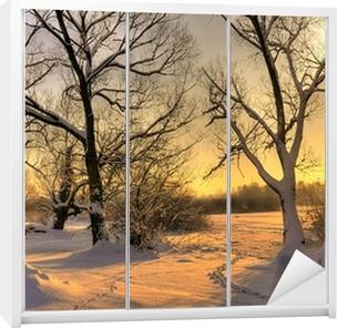 Smuk vinter solnedgang med træer i sneen Garderobe klistermærke