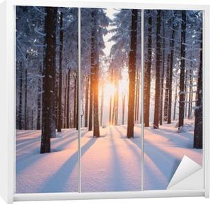 Solnedgang i skoven i vinterperioden Garderobe klistermærke