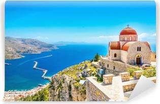 Etäinen kirkko punaisella katolla kalliolla, kreikassa Itsestäänkiinnittyvä Valokuvatapetti