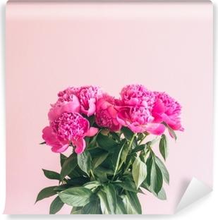 Kimppu ihastuttavia pioniita vaaleanpunaisella taustalla. Itsestäänkiinnittyvä valokuvatapetti