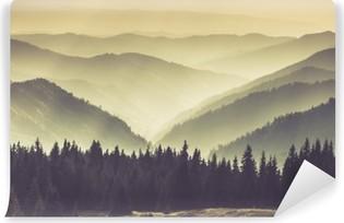 Maisema sumuisten vuorten kukkuloille. Itsestäänkiinnittyvä valokuvatapetti