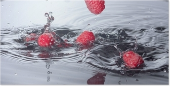Punaiset vadelmat pudotettiin veteen roiskeella Juliste