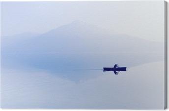Sumu järven yli. siluetti vuoret taustalla. mies makaa veneessä meloa. Kangaskuva