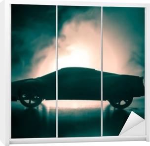 Klesskapklistremerke Bilen i skyggene med lysende lys i svakt lys, eller silhuett av sportbil mørk bakgrunn