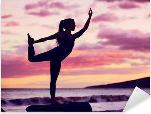 Kvinde praktiserer yoga på stranden ved solnedgang Pixerstick klistermærke