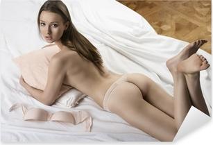Sexet nøgen pige ligger på den hvide seng med pude i hendes arme Pixerstick klistermærke