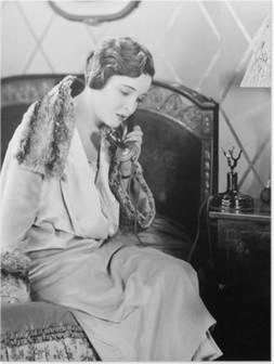 Nuori nainen istuu sängyllään makuuhuoneessa puhuessaan puhelimessa Korkealaatuinen Juliste