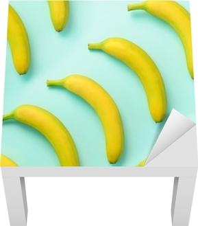 Lack-Tischaufkleber Buntes Fruchtmuster. Bananen über blauem Hintergrund. Draufsicht Pop-Art-Design, kreatives Sommerkonzept. minimaler flacher Laienstil.
