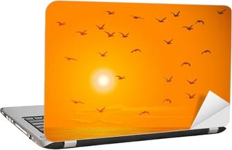 Laptop Sticker Vliegende vogels tegen oranje zonsondergang.