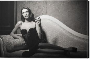 Leinwandbild Film-Noir-Stil: elegante junge Frau liegt auf dem Sofa und das Rauchen von Zigaretten. Schwarz und weiß