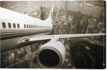 Leinwandbild Flugzeugstart über der Stadt