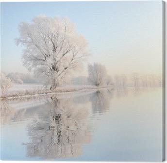 Leinwandbild Frosty Winter Baum gegen einen blauen Himmel mit Reflexion in Wasser