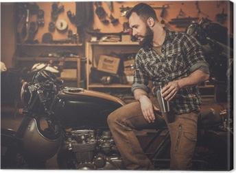 Leinwandbild Mann und Vintage-Stil Café-Rennläufer-Motorrad in der Garage