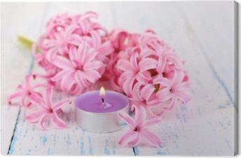 Leinwandbild Rosafarbene Hyazinthe mit Kerze auf Holzuntergrund