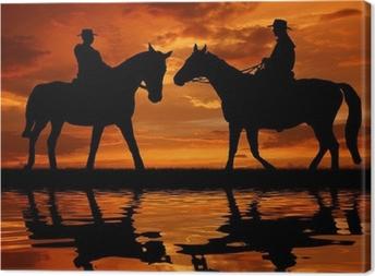 Leinwandbild Silhouette Cowboys mit Pferden in den Sonnenuntergang