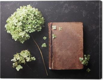 Leinwandbild Stillleben mit alten Buch und getrockneten Blumen Hortensie auf schwarzem Vintage Tisch Draufsicht. Wohnung lag Styling.