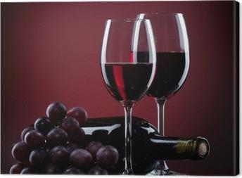 Leinwandbild Wein in Gläser mit Traube und Flasche auf rot