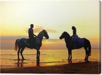 Leinwandbild Zwei Fahrer auf dem Pferd bei Sonnenuntergang am Strand. Liebhaber fahren hors