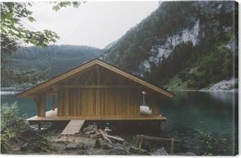Lerretsbilde Vedhus på innsjø med fjell og trær