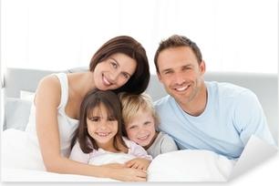 Naklejka Pixerstick Portret szczęśliwa rodzina siedzi na łóżku